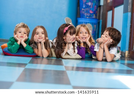 Cute little children lying in a row on floor in classroom - stock photo