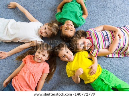 Cute little children lying on floor in kindergarten - stock photo