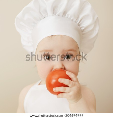 cute little cook eats tomato - stock photo
