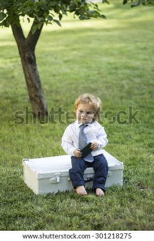 Cute little curious boy kid with blonde curly hair in formal clothes with tie sitting on green grass and tree on white vintage briefcase playing on mobile phone outdoor sunny day copyscape, vertical - stock photo