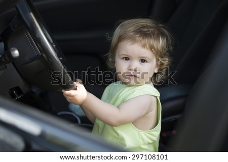 Cute little curious male child driver sitting in big car with black salon holding wheel looking forward through window in summer, horizontal picture - stock photo