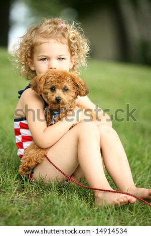 Cute little curly blonde girl and a loving puppy - stock photo