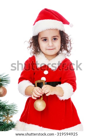 Cute little curly-haired girl in a suit and hat of Santa Claus. The girl is holding in front of a Christmas toy. Closeup-Isolated on white background