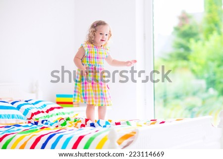 Cute little curly toddler girl in a colorful dress jumping on a big white  bed laughing. Children Jump On Bed Cute Little Stock Photo 292081058   Shutterstock