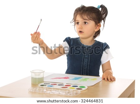 Cute little dark-haired girl with short pigtails on her head paints with watercolors. Girl holding at arm's length the brush and looks with surprise at her. The plan-Isolated on white background - stock photo