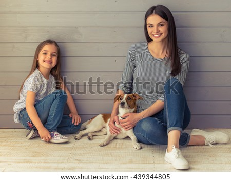 Cute little daughter and her beautiful young mother are looking at camera and smiling while posing with their dog - stock photo