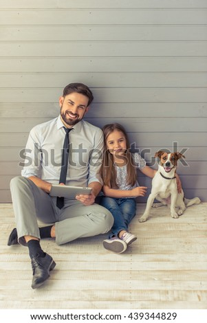 Cute little daughter and her handsome young father are looking at camera and smiling while posing with their dog. Dad is using a tablet - stock photo