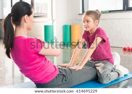 Cute little daughter looking at mother exercising on mat in gym