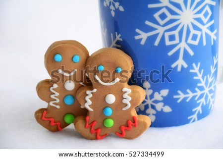 Cute little decorated gingerbread men with snowflake mug of hot chocolate for a Christmas treat