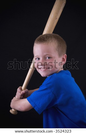 Cute little eight year old boy holding a baseball bat. - stock photo