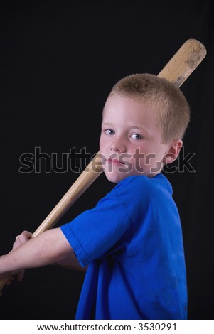 Cute little eight year-old boy ready to swing the bat. - stock photo