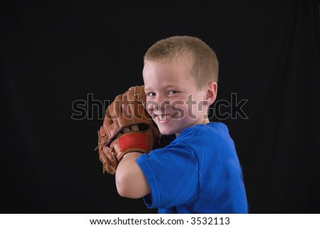 Cute little eight year old boy with a ball and a glove. - stock photo