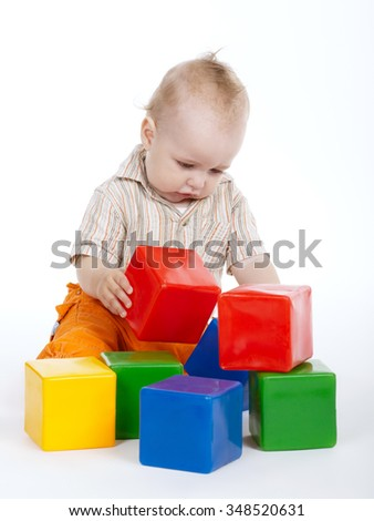 cute little engineer plays with cubes on white - stock photo