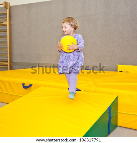 Cute little European toddler girl having fun at indoor playground. - stock photo