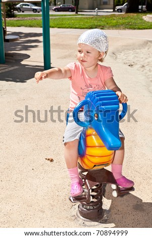 Cute little European toddler girl having fun at the playground in the park. - stock photo
