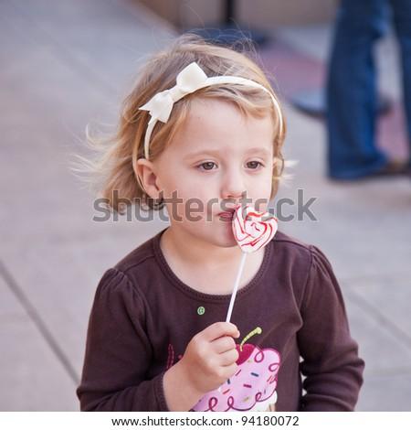 Cute little European toddler girl having fun eating heart shaped lollypop - stock photo