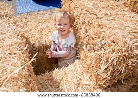 Cute little European toddler girl having fun on pumpkin patch. - stock photo