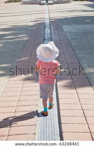 Cute little European toddler girl walking along the line. - stock photo