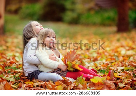 Cute little fashion sisters hugging and kissing in autumn park - stock photo