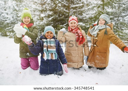 Cute little friends playing snowballs in winter park - stock photo