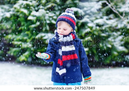 Cute little funny boy in colorful winter clothes catching snow and snowflakes, outdoors during snowfall. Active outdoors leisure with children in winter. Kid with warm hat, hand gloves and scarf  - stock photo