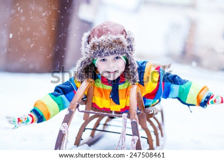 Cute little funny boy in colorful winter clothes having fun on snow sledge, outdoors during snowfall. Active outdoors leisure with children in winter. Kid with warm hat, hand gloves and scarf  - stock photo