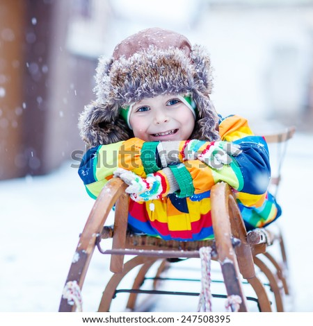 Cute little funny boy in colorful winter clothes sliding on snow sledge, outdoors during snowfall. Active outdoors leisure with children in winter. Kid with warm hat, hand gloves and scarf  - stock photo
