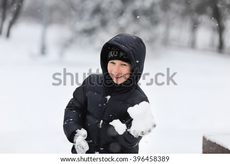 Cute little funny boy in winter clothes having fun with snowballs, outdoors during snowfall. Active outdoors leisure with children in winter. Child, kid playing with snow in park. - stock photo