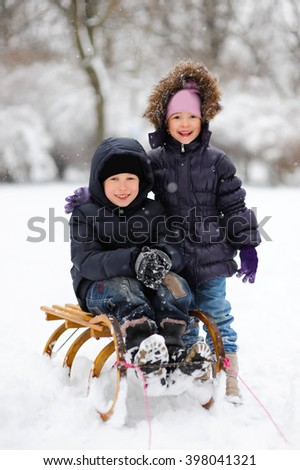 Cute little funny boy sledding, having fun on snow in winter, outdoors during snowfall. Active outdoors leisure with children in winter. Happy little kid is playing in snow, good winter weather.