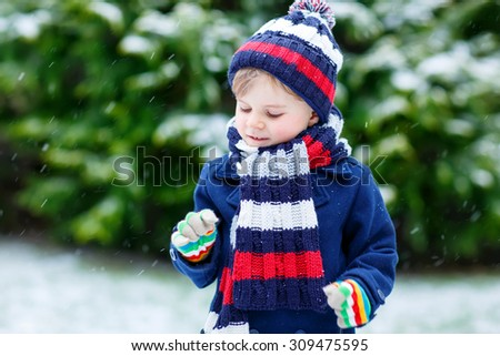 Cute little funny child in colorful winter clothes having fun with snow, outdoors during snowfall on cold day. Active outdoors leisure with children in winter. - stock photo