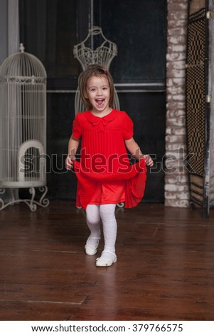 Cute little girl about four years old in a red dress  - stock photo