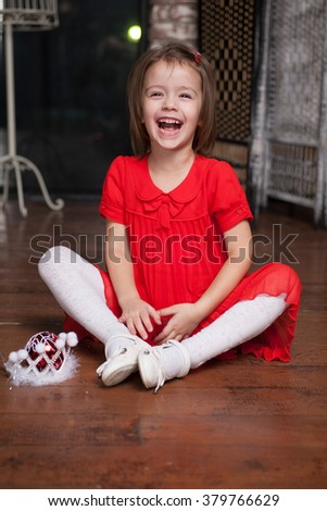 Cute little girl about four years old in a red dress sitting on the floor and smiling - stock photo