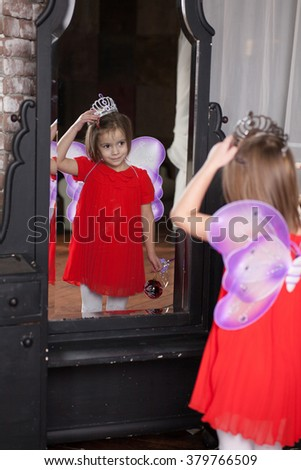 Cute little girl about four years old in fairy costume looking at herself in the mirror - stock photo