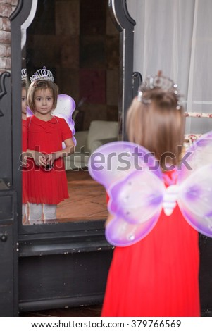 Cute little girl about four years old in fairy costume looking in the mirror - stock photo