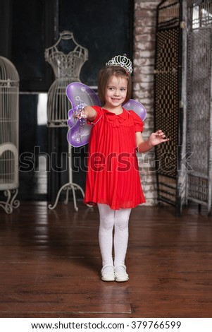 Cute little girl about four years old in fairy costume playing with a magic wand - stock photo