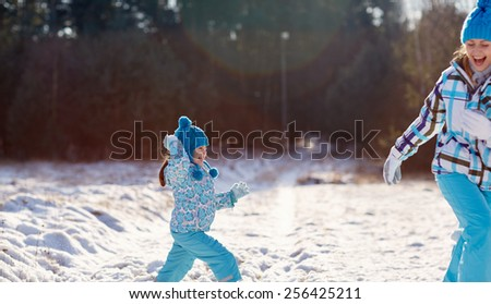 Cute little girl about to throw a snowball at her laughing mother outdoors on a winter's day - stock photo