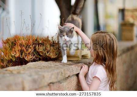 Cute little girl and a cat outdoors on hot summer day in Italy