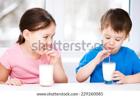 Cute little girl and boy drink tasty fresh milk - stock photo