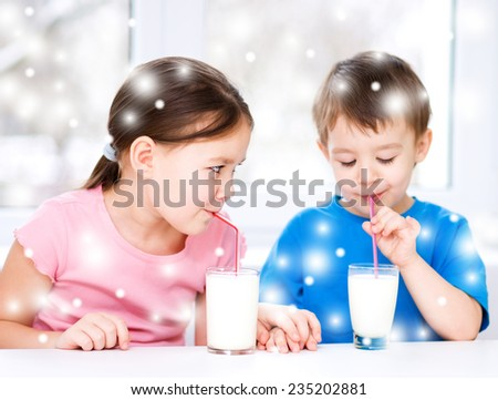 Cute little girl and boy drink tasty fresh milk, over snowy background - stock photo