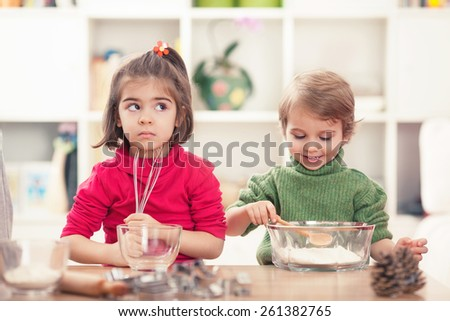 Cute little girl and boy learning how to bake cookies - stock photo