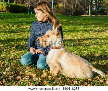 Cute little girl and dog sitting on the grass in a park in autumn