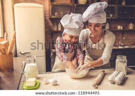 Cute little girl and her beautiful mother in chef hats are kneading dough and smiling while preparing it for baking