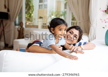 Cute little girl and her beautiful mother playing at home - stock photo