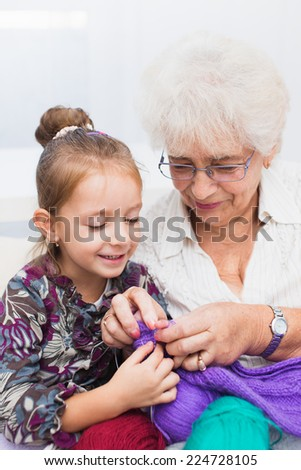 cute little girl and her granddaughter knitting together - stock photo