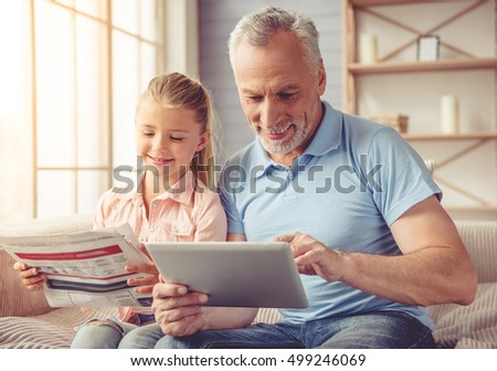 Cute little girl and her handsome grandpa are smiling while sitting on couch at home. Girl is reading a newspaper while grandpa is using a tablet