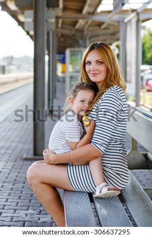 Cute little girl and her mother on a railway station. Kid and woman waiting for train and happy about a journey. People, travel, family, lifestyle concept - stock photo