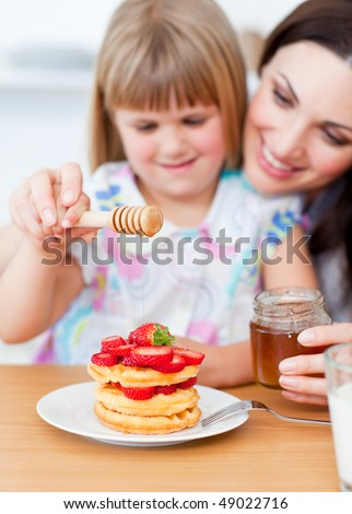 Cute little girl and her mother putting honey on waffles in the kitchen