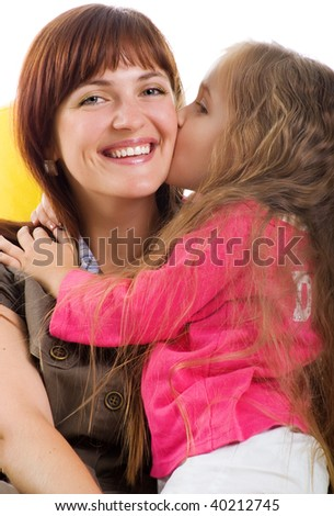 Cute little girl and her smiley mother. Studio shot
