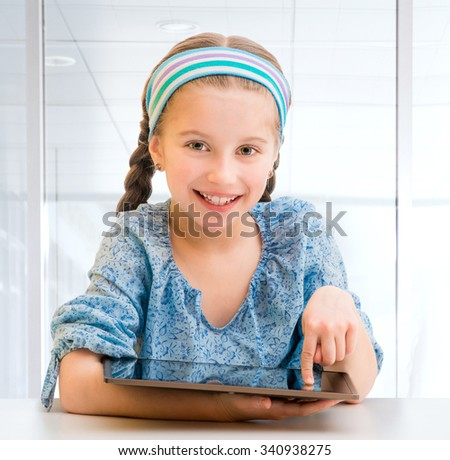 Cute little girl and her tablet - stock photo