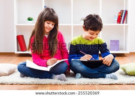 Cute little girl and little boy are doing their homework.Homework - stock photo